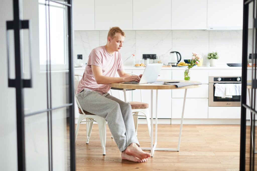 Young casual man sitting by table in the kitchen in front of laptop